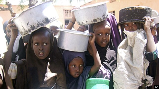 Displaced Somali children line up, containers in hand, to receive food aid in Mogadishu, March 15, 2011
