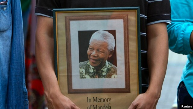FILE - A man holds a tribute photograph as he watches the funeral service for former South African President Nelson Mandela on a large screen television  in Cape Town, December 15, 2013.