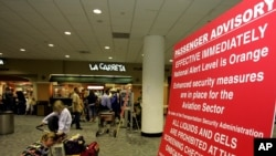FILE - A woman organizes her carry-on luggage next to a sign explaining new security measures at Miami International Airport.