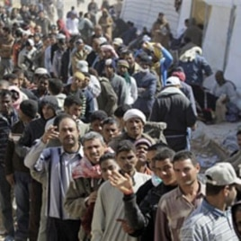 People who used to work in Libya and fled the unrest in the country, wait to receive clothes, at the Tunisia-Libyan border, in Ras Ajdir, Tunisia, Mar 3 2011