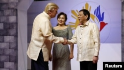 U.S. President Donald Trump shakes hands with Philippines President Rodrigo Duterte as he arrives for the gala dinner marking ASEAN's 50th anniversary in Manila, Nov. 12, 2017.