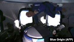 Jeff Bezos di dalam penerbangan Blue Origin, berusaha menangkap popcorn dengan mulutnya. (AFP PHOTO / Blue Origin)