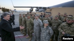 Петро Порошенко з американськими військовослужбовцями, які доставили американську військову техніку