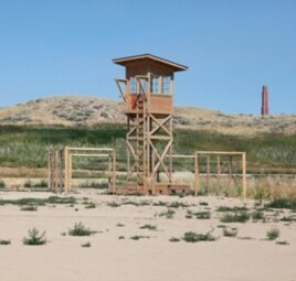 A replica of one of the camp's watch towers in the exact place where it once stood. The smoke stack of the hospital is in the background.