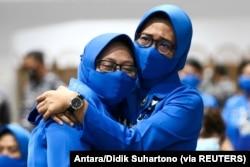 The family of the sunken KRI Nanggala-402 submarine crew members react as they hug at Koarmada II fleet office in Surabaya, East Java Province, Indonesia April 25 2021