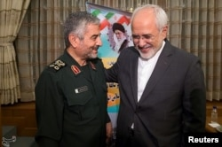 Islamic Revolutionary Guard Corps (IRGC) commander Mohammad Ali Jafari, left, and Iran's Foreign Minister Mohammad Javad Zarif smile during a coordination meeting for the 40th anniversary of the Islamic Revolution, in Tehran, Iran, Oct. 9, 2017.