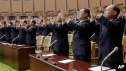 In this image made from video released April 11, 2017, by North Korean broadcaster KRT, officials stand and applaud as North Korean leader Kim Jong Un presides over parliament in Pyongyang, North Korea.