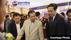 Prime Minister Hun Sen, center, and Commerce Minister Pan Sorasak, right, are pictured together at a trade expo, Phnom Penh, Cambodia, December 15, 2017. (Photo courtesy of Ministry of Commerce)