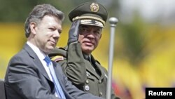 El director de la policía colombiana, José Roberto León, saluda desde un auto militar, mientras acompaña al presidente Juan Manuel Santos.