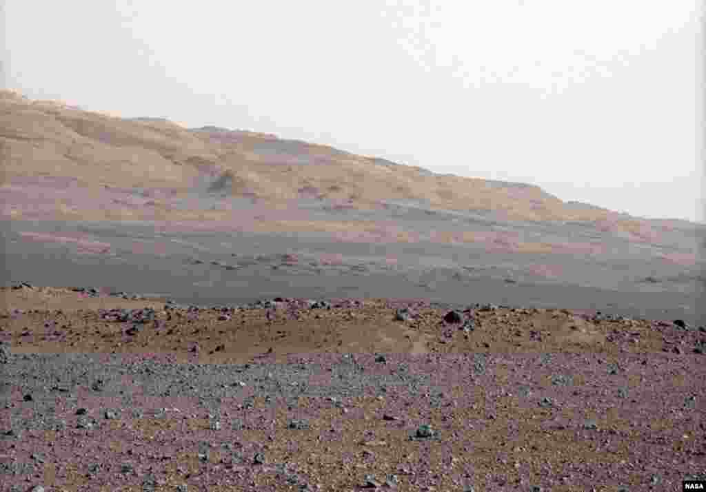 The gravelly area around Curiosity's landing site is in the foreground. Beyond the swale is the red-brown rim of an impact crater. Further in the distance, there are dark dunes and the layered rock at the base of Mount Sharp.