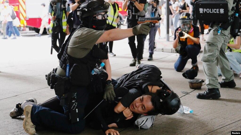 香港警察在逮捕一名参加反对港版国安法游行示威者的同时举起手中的胡椒喷剂手枪。(2020年7月1日)
