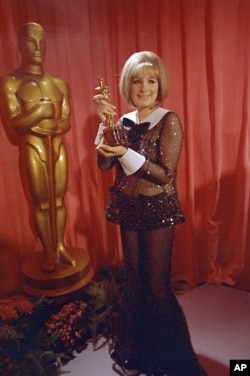 "Actress and singer Barbra Streisand wears a sequined Arnold Scaasi bell-bottomed sheer pantsuit as she poses with her Oscar for her role in ""Funny Girl"" at the 41st Academy Awards in Los Angeles, April 14, 1969."