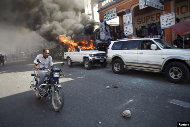 A man riding a bike passes next to a car that was set afire by protesters during a demonstration against the electoral process in Port-au-Prince, Haiti, Jan. 18, 2016.