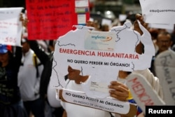 "FILE - Reinaldo Olivares, a kidney transplant patient, holds a placard with the shape of the map of Venezuela that reads, ""Humanitarian emergency. I do not want to lose my organ,"" during a protest against medicinal shortages in Caracas, Venezuela, Feb. 8,"