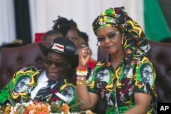 FILE - Zimbabwean first lady Grace Mugabe, right, is seen with her husband, President Robert Mugabe, at a rally in Gweru, Zimbabwe, Sept, 1, 2017.