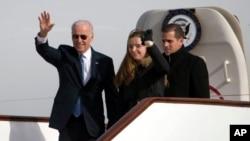 Wakil Presiden Joe Biden melambaikan tangannya saat keluar dari pesawat Air Force Two dengan cucunya Finnegan Biden dan putranya Hunter Biden di bandar udara Beijing, China (4/12). (AP/Ng Han Guan)
