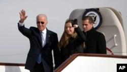 在北京国际机场,美国副总统拜登在孙女和儿子的陪伴下走下飞机,向迎候者挥手致意。(2013年12月4日)
