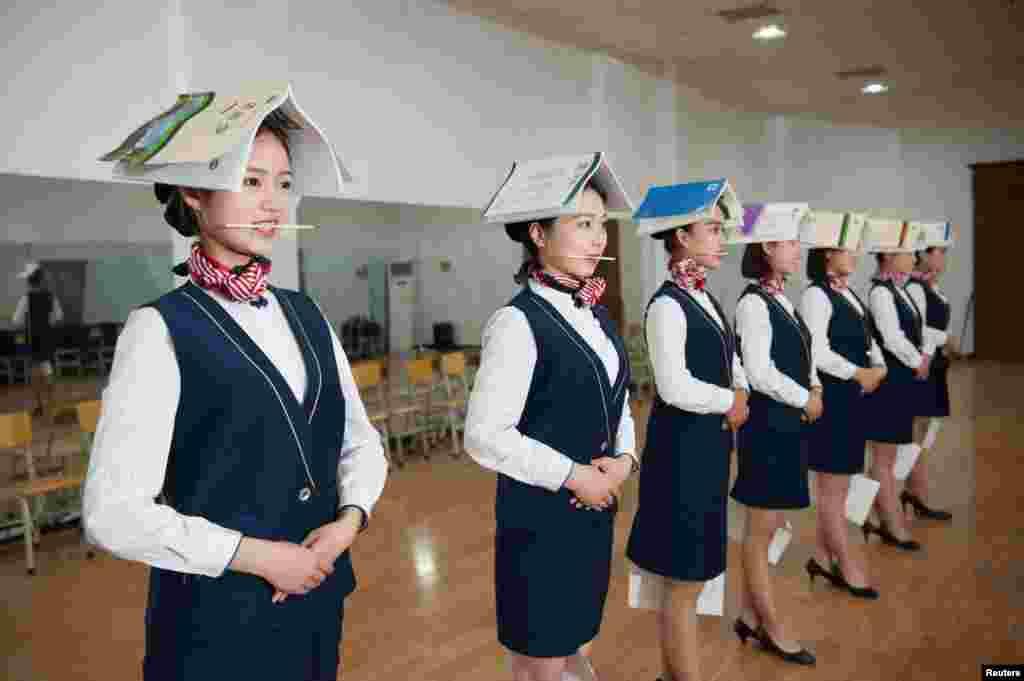 Para siswi sekolah pramugari melakukan latihan posisi berdiri sambil tersenyum (menggigit sumpit) dan menjepit kertas di kakinya, pada sekolah pramugari di Shijiazhuang, Hebei, China.