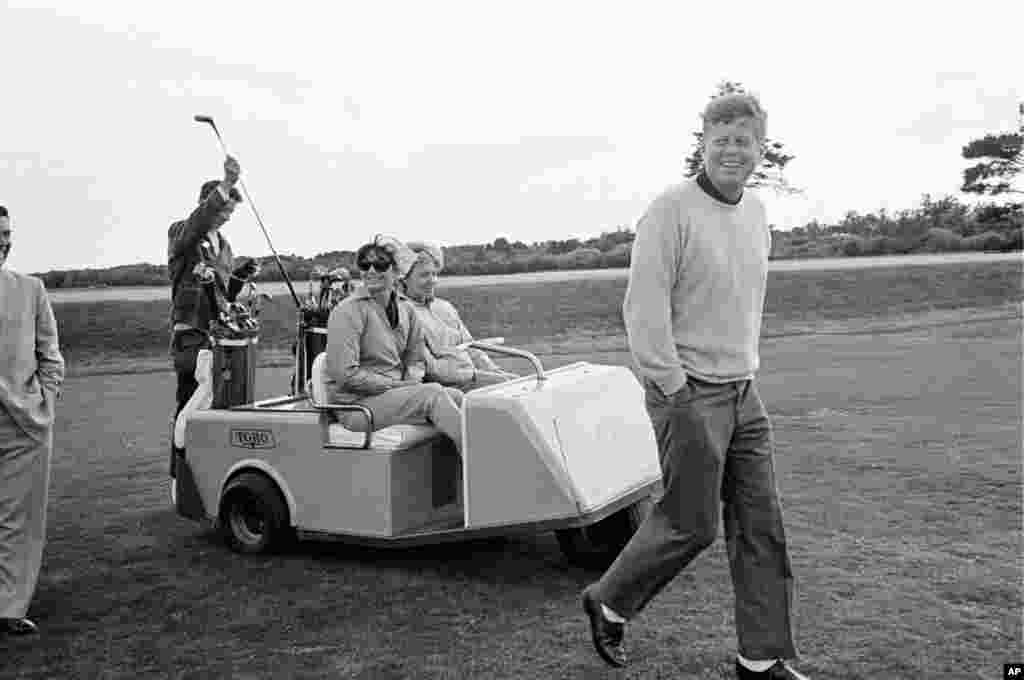 President Kennedy walks along the golf course after driving off from the tenth tee at the Country Club in Newport, Rhode Island, September 14, 1963. Mrs. Jacqueline Kennedy and Mrs.Tony Bradlee, wife of Washington Post senior editor Ben Bradlee, ride alon