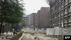 Khói bốc lên và gạch đá đổ nát văng ra đường sau vụ nổ tại tòa nhà chính phủ ở Oslo