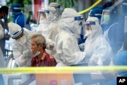 A health worker collects sample for new coronavirus testing from a man at the newly locked down area in Kuala Lumpur, Malaysia, on Friday, May 15, 2020.