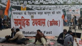 Protestors sits in front of a banner during a protest against last month's gang rape and murder of a student, in New Delhi, February 2, 2013.
