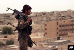 This April 30, 2017, photo provided by the Syrian Democratic Forces (SDF) shows a fighter from the SDF carrying weapons as he looks toward the northern town of Tabqa, Syria.