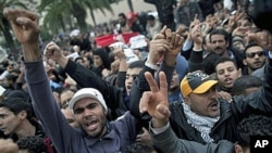 Tunisian protesters shout slogans in front of the RCD party office after the sign bearing its name was dismantled, in Tunis, 20 Jan 2011