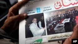 Seorang warga Mesir tengah memegang surat kabar Al-Ahram di Kairo, Mesir (20/8) yang menampilkan gambar pemimpin Ikhwanul Muslimin Mohammed Badie (kiri) di halaman depan (Foto: dok). Pengadilan Mesir menunda sidang atas Muhammad Badie dan dua wakilnya, Minggu (25/8).