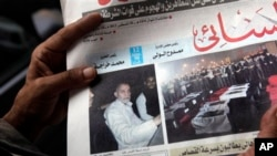 8月20日,开罗一个埃及人在看报纸,报上登的照片是穆斯林兄弟会最高领导人巴迪(左)和被杀害的埃及警察的灵柩(右)。
