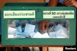An election commission official holds a ballot paper from a ballot box while counting votes during a constitutional referendum vote at a polling station in Bangkok, Aug. 7, 2016.