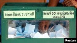 Seorang pejabat komisi pemilu memegang kertas suara dari kotak suara sambil menghitung perolehan suara dalam referendum konstitusi di TPS, Bangkok, 7 Agustus 2016. (Foto: dok).
