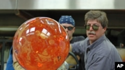 Glass artist Josh Simpson turns one of his signature planet-like spheres after heating it in a furnace.