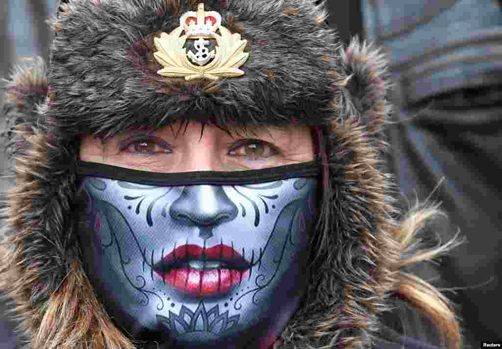 """A woman wearing a protective face mask joins former British armed forces members and supporters at a """"Respect Our Veterans"""" parade and rally in London, May 8, 2021."""