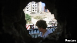A woman is seen from a hole in her home's wall, caused by clashes between Sunni Muslims and Alawites in Tripoli, northern Lebanon, August 27, 2012.