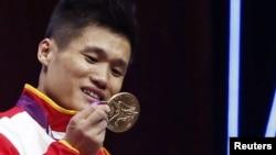 Lu Xiaojun mengamati medali emas yang diperolehnya untuk cabang angkat besi putra kelas 77 koligram di Olimpiade London 2012 (1/8).