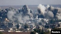 Asap membubung di atas kota Kobani di Suriah setelah serangan udara Koalisi AS, dilihat dari perbatasan Turki dan Suriah (18/10).