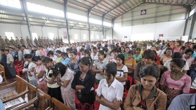 Released prisoners stand up before Burma's prison department chief Zaw Win speaks in a hall at Insein Prison in Rangoon, May 17, 2011.