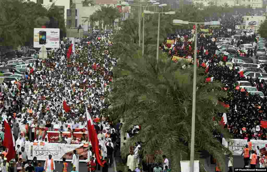 Miles de manifestantes anti gobierno protestan en una avenida a las afueras de Manama, Bahréin, con banderas del país mientras cantan mensajes contra el régimen, durante el primer día de prácticas del Fórmula Uno