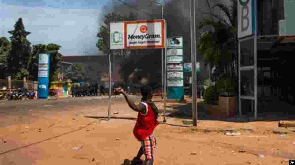Un jeune burkinabé jette une pierre sur des policiers lors de la manifestation contre le président du Burkina Faso dont le gouvernement tente de modifier la constitution pour un nouveau mandat à la tête du pays, Ouagadougou, au Burkina Faso, le mardi 28 octobre 2014.