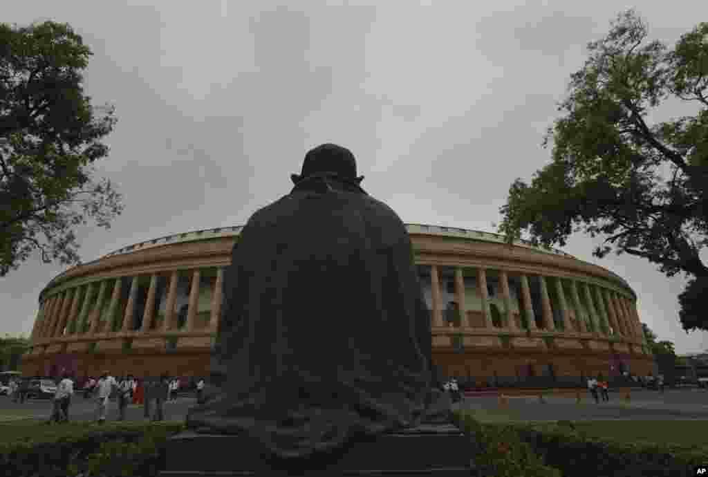 نمایی از پارلمان هند و مجسمه گاندی که به این ساختمان مینگرد. دوره جدید قانونگذاری هند شروع شده است.