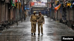 Indian policemen patrol a deserted street during a strike called by separatists to mark India's 67th Independence Day in Srinagar, August 15, 2013.