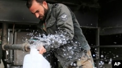 In this Jan. 16, 2017 photo, man fills a plastic container with water from a tap water in Damascus, Syria. Water cut-offs have been almost continuous since Dec. 22, in the worst water crisis known to Damascus residents