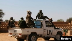 FILE - Chadian U.N. peacekeepers gesture as they patrol in Aguelhok, Mali, Jan. 24, 2014.