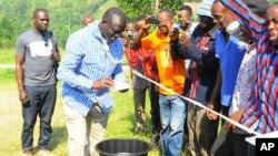 Le leader de l'opposition ougandaise Kizza Besigye nettoie ses mains après avoir voté à son bureau de vote près de sa maison de campagne dans Rukungiri environ 700 kilomètres à l'ouest de Kampala, Ouganda, 18 février 2016.