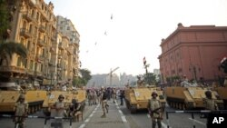 FILE - Egyptian military helicopters fly overhead as army soldiers stand guard at an entrance to Tahrir Square, in Cairo, Egypt, Oct. 6, 2013. The United States on July 26, 2018, released $195 million in military aid to Egypt that had been withheld because of concerns about the country's human rights record.