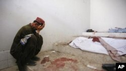 A man mourns next to his dead relative at a morgue, after his body was recovered from the site of a double suicide bombing in Quetta, Pakistan, September 7, 2011.