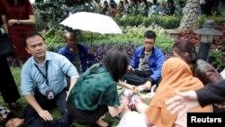 Korban luka dirawat di luar gedung Bursa Efek Indonesia setelah lantai di gedung itu ambruk, 15 Januari 2018. (REUTERS/Darren Whiteside)