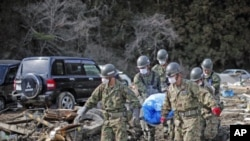 Members of the Japan Self-Defense Force carry the body of a victim found amid the rubble in Noribu, northern Japan, as pressure mounts to expand an evacuation zone around the crippled nuclear plant where radioactive iodine was detected in the groundwater