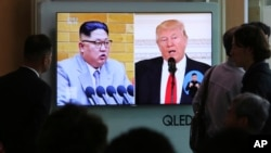 People watch a TV screen showing President Donald Trump, right, and North Korean leader Kim Jong Un during a news program at the Seoul Railway Station, April 21, 2018. North Korea said it has suspended nuclear and long-range missile tests and plans to close its nuclear test site.